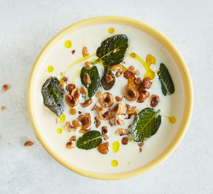 Cauliflower soup with sage leaves and hazelnuts in bowl