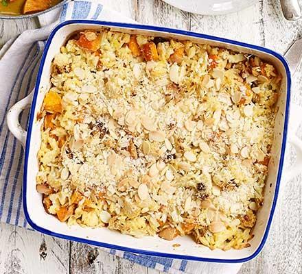 A white and blue casserole dish serving cauliflower, squash & orzo gratin