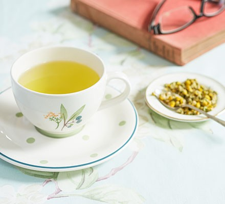 Camomile tea with honey served in a teacup