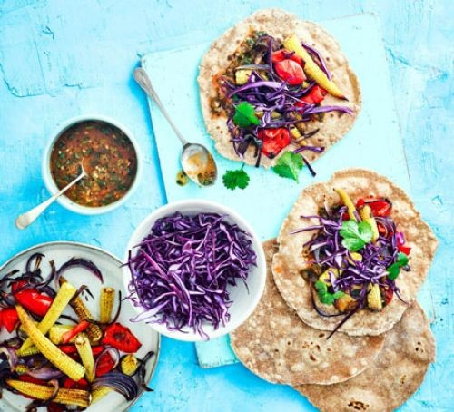 Tacos filled with bright vegetables plus pots of dips