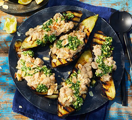 Charred aubergines with white beans & salsa verde served on a plate