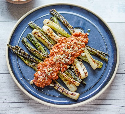 Spring onions with romesco sauce on a plate, on a table