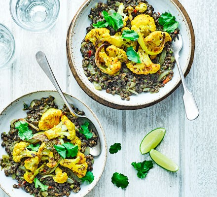 Two bowls containing black dhal topped with cauliflower