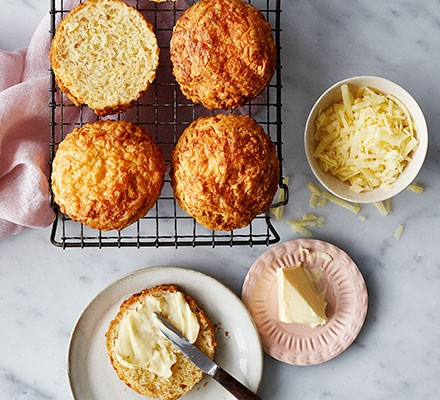 Classic cheese scones served on a wire rack with butter alongside