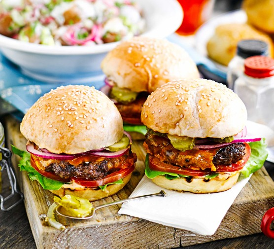 Three cheeseburgers on a chopping board outdoors