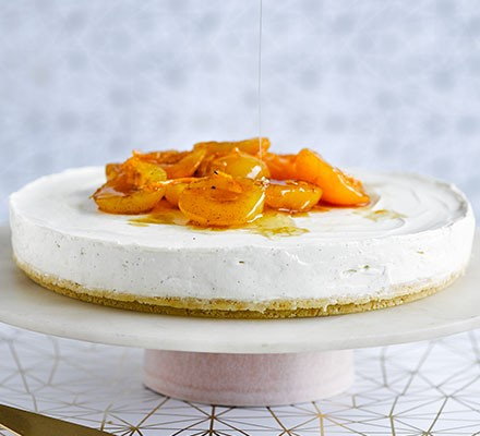 Yogurt cheesecake with honey-roasted apricots served on a cake stand