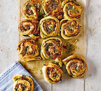 Cheese and pesto swirl buns on a wooden board
