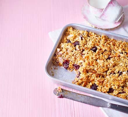 Cherry & coconut flapjacks traybake on a pink table
