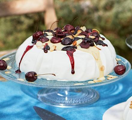 Cherry, almond & vanilla custard pavlova served on a cake stand
