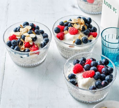 Three pots of overnight oats topped with mixed berries and almonds
