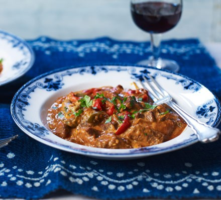 Curry with chillies in bowl with fork and glass of wine