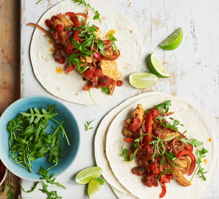 Chicken tortillas with salad and limes on board