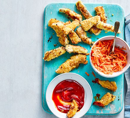 Crispy chicken strips served with a carrot salad and dipping sauce