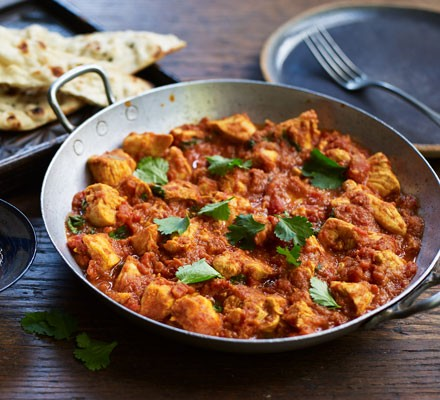 Chicken Madras curry in a balti dish with naan bread