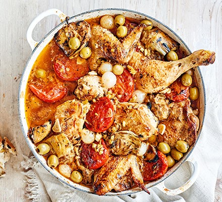 A casserole dish serving chicken Provençal with olives & artichokes