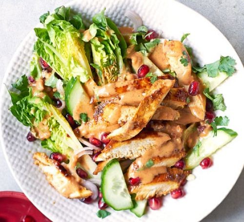 Chicken satay pieces with salad leaves