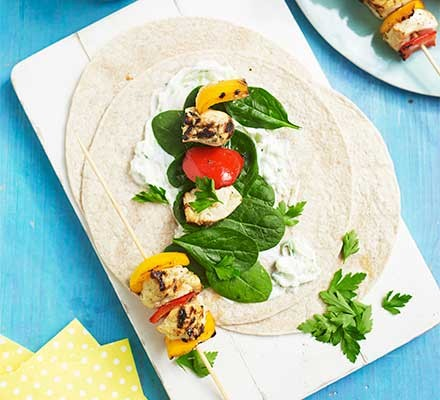 Tortillas topped with chicken skewers and tzatziki on a blue table