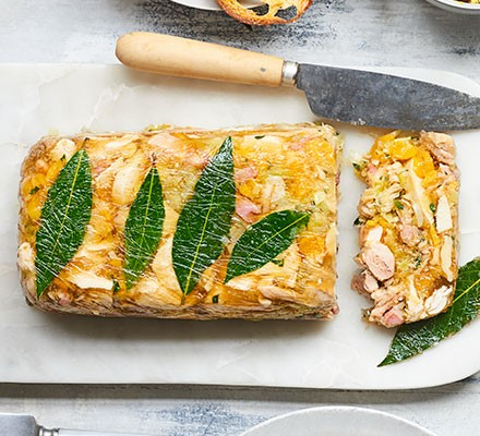 Chicken terrine with leeks & apricots on a platter with knife