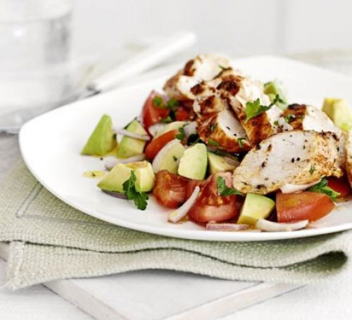 Chicken breast with avocado and tomato salad on a plate