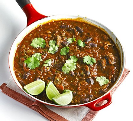 Chilli in pan with herbs and lime wedges