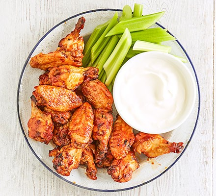 Chilli-maple chicken wings served with celery and sour cream