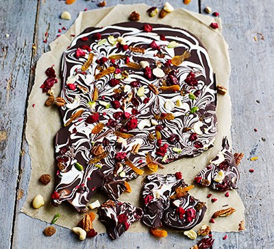 Chocolate bark with fruit and nuts on parchment paper