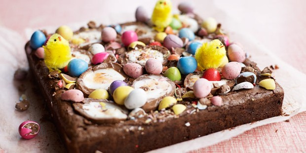 Chocolate brownie traybake topped with mini eggs, creme eggs and toy chicks