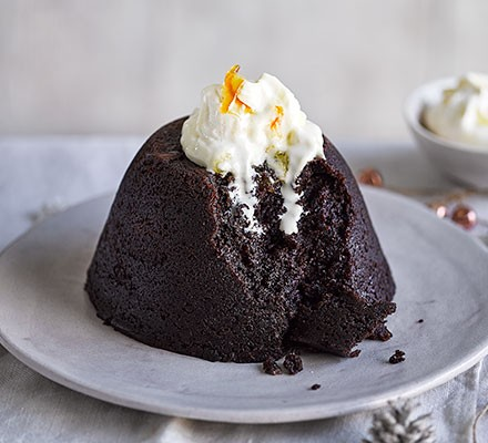Chocolate & marmalade steamed pudding served on a plate with marmalade cream