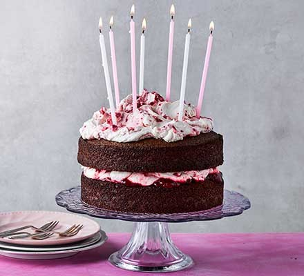 Chocolate & raspberry birthday layer cake served on a cake stand