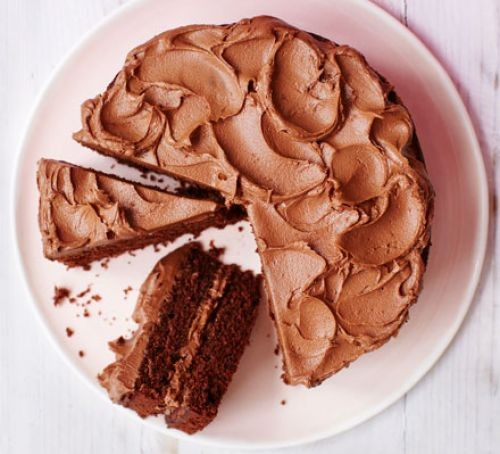 Chocolate sponge cake on a white plate with two slices cut out