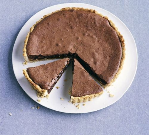 Baked chocolate tart with two slices cut out, on a plate