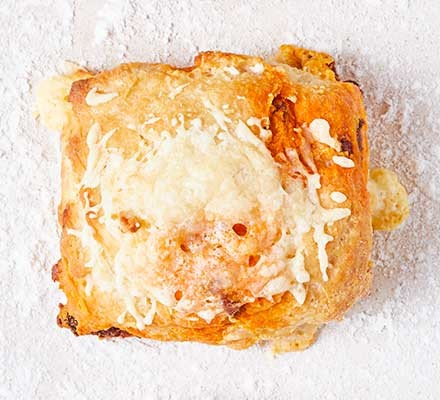 A chorizo & manchego scone on a floured surface