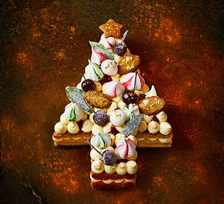 Christmas tree-shaped cake topped with meringues and biscuits