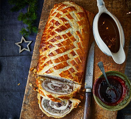 Christmas dinner Wellington cut into slices and served on a wooden board with a jug of gravy