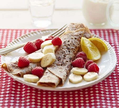 Rolled up crepe with sliced bananas and raspberries on a plate