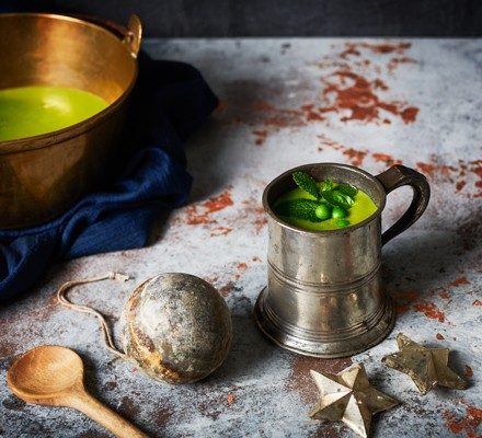 Metal jug and bowl filled with green vegetable soup, next to wooden spoon