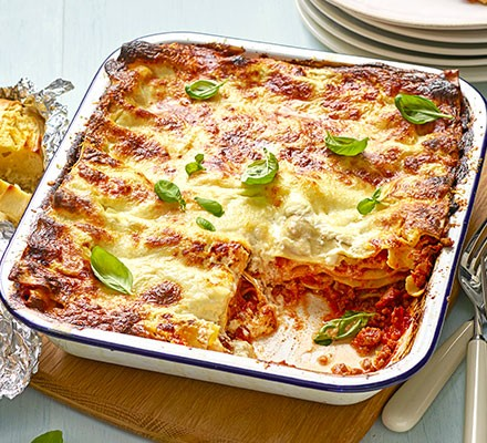 Classic lasagne in an oven dish topped with basil leaves