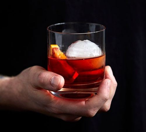 Negroni cocktail with orange and ice in glass