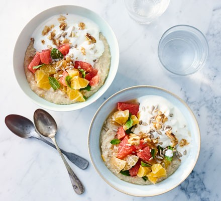 Two bowls of clementine and vanilla porridge with fresh fruit