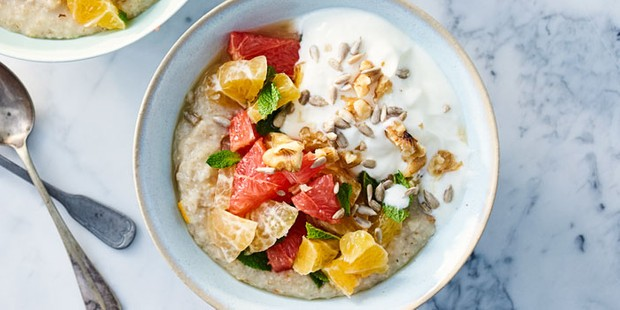 A small blue bowl of porridge topped with fruit, seeds and yogurt