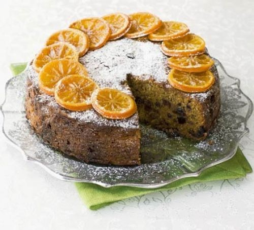 Fruit cake topped with a ring of clementine slices, served on a glass dish