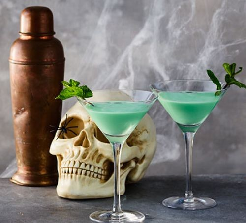 Two glasses of blue cocktail next to skull and mixer