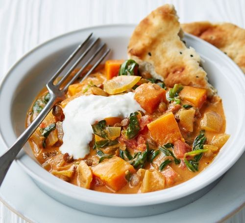 Squash curry with yogurt in bowl and naan bread