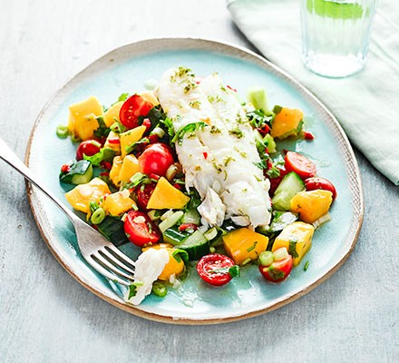 A plate of cod with cucumber, avocado & mango salsa salad