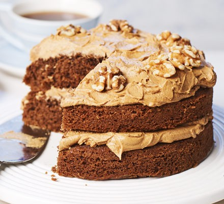 Coffee cake with buttercream and nuts on stand