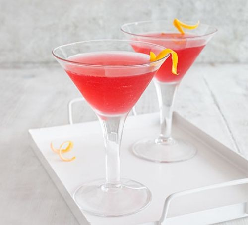 Pink cocktail in glass with orange peel