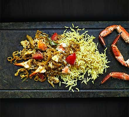 A serving board with crab curry, rice and crabs legs