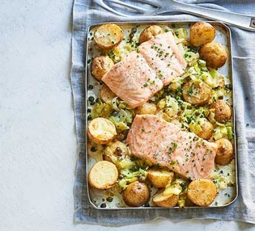 Salmon fillets with leek and potatoes on a baking tray