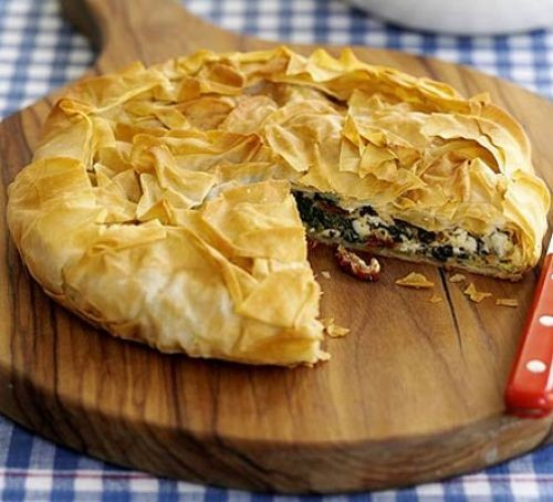 Greek-style feta and spinach filo pie with slice cut out