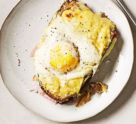 A croque madame served on a plate, topped with egg